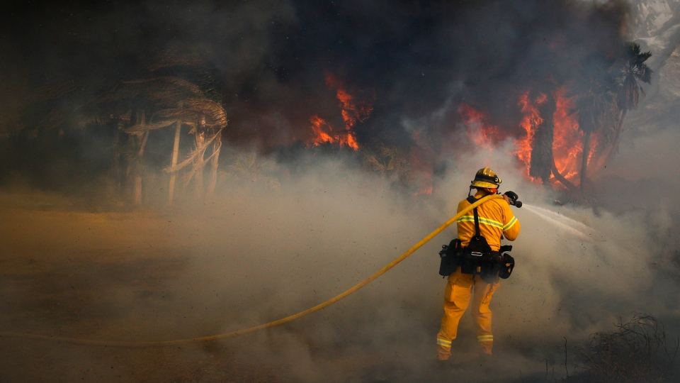 A firefighter battles a wildfire at Faria State Beach in Ventura, Calif., Thursday, Dec. 7, 2017. (AP Photo / Jae C. Hong)