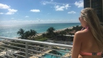 This March 13, 2017 photo shows Louise Reed looking out at a view of a pool and ocean from the Grand Beach Hotel in Miami Beach, Fla. The South Beach neighborhood can be a great destination for a family with teenagers, even on a budget, if you mix pool time and beach time with shopping, people-watching and dining at some of the less expensive venues. (Maggie Delehanty via AP)