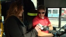 Forest Atkinson hands a chocolate Turtle and a card to an OC Transpo operator. (CTV Ottawa)