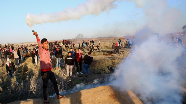 A Palestinian protester throws back a teargas canister that was fired by Israeli soldiers, during clashes on the Israeli border following a protest against U.S. President Donald Trump's decision to recognize Jerusalem as the capital of Israel, east of Gaza City, Friday, Dec. 8, 2017. (AP / Adel Hana)