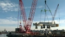Massive crane lifts new bridge pieces into place