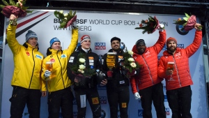 Second placed Germans Thorsten Margis and Francesco Friedrich, Swiss winners Clemens Bracher and Michael Kuonen and Canada's third placed Chris Spring and Neville Wright celebrate on the podium after the men's two person bobsled World Cup in Winterberg, Germany, Saturday, Dec. 9, 2017. (Caroline Seidel / dpa)