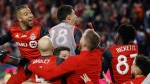 The Toronto FC celebrate a goal by midfielder Victor Vazquez (obscured) in stoppage time against the Seattle Sounders during second half MLS Cup Final soccer action in Toronto on Saturday, December 9, 2017. THE CANADIAN PRESS/Mark Blinch