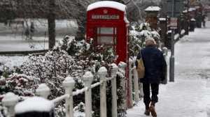 A man walks past a snow covered phone box in Marlow, England, after heavy snow fell across parts of the UK, Sunday Dec. 10, 2017. (Steve Parsons/PA via AP)