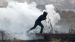 A Palestinian protester runs for cover from teargas fired by Israeli troops during clashes on the Israeli border with Gaza, Sunday, Dec. 10, 2017. (AP Photo/ Khalil Hamra)