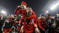 Toronto FC forward Sebastian Giovinco (10) and midfielder Jonathan Osorio gesture to the crowd as the Toronto FC celebrate their win over the Seattle Sounders in the MLS Cup Final soccer action in Toronto on Saturday, December 9, 2017. THE CANADIAN PRESS/Mark Blinch