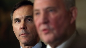 Federal Finance Minister Bill Morneau, left, listens as Parliamentary Secretary to the Minister of Justice Bill Blair talks to reporters, before joining their federal, provincial and territorial counterparts for dinner in Ottawa, Sunday, December 10, 2017. (THE CANADIAN PRESS/Fred Chartrand)