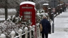 A man walks past a snow covered phone box in Marlow, England, after heavy snow fell across parts of the UK, Sunday Dec. 10, 2017. Snow is causing travel disruptions across central England and northern Wales, grounding some flights and shutting down roads. (Steve Parsons/PA via AP)