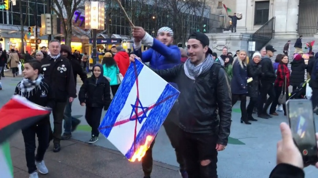 A pro-Palestinian demonstrator holds a burning cardboard sign painted in the likeness of the Israeli flag.