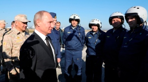 Russian President Vladimir Putin, 2nd left, and Defence Minister Sergei Shoigu, left, chat with Russian military pilots at the Hemeimeem air base in Syria, on Monday, Dec. 11, 2017. (Mikhail Klimentyev, Sputnik, Kremlin Pool Photo via AP)
