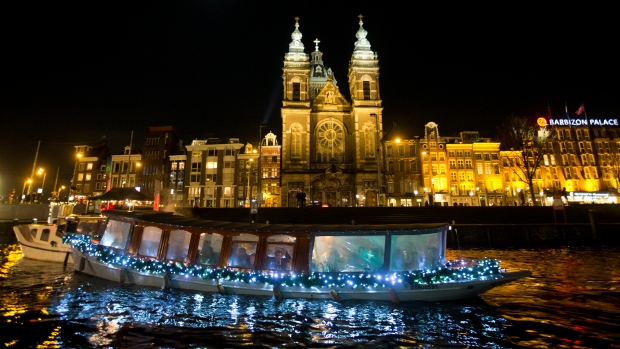 Canal cruise boats pass St. Nicholas Basilica in the center of Amsterdam, Netherlands on Nov. 30, 2017. (AP Photo/Peter Dejong)