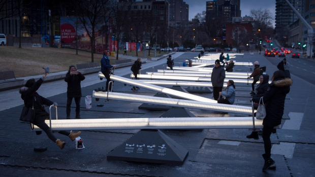People play on a series of 30 interactive seesaws with light and sound that changes when in motion at the Place des Festivals on Dec. 8, 2017 in Montreal. THE CANADIAN PRESS/Paul Chiasson