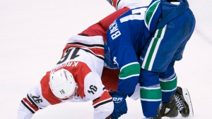 Carolina Hurricanes centre Marcus Kruger (16) goes over Vancouver Canucks left wing Sven Baertschi (47) during second period NHL action in Vancouver, Tuesday, Dec. 5, 2017. (THE CANADIAN PRESS/Jonathan Hayward)