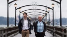 A pigeon flies past Prime Minister Justin Trudeau, left, as he and South Surrey-White Rock Liberal byelection candidate Gordie Hogg walk along the pier in White Rock, B.C., on December 2, 2017. (THE CANADIAN PRESS / Darryl Dyck)