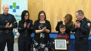 "First responders, including 911 operator Monica Grela (second from left) applaud Ronan Male for receiving the ""Citizen Life-Saving Award."" (CTV Edmonton)"