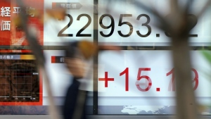 A man walks past an electronic stock board showing Japan's Nikkei 225 index at a securities firm in Tokyo Tuesday, Dec. 12, 2017. (AP Photo/Eugene Hoshiko)