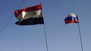 In this Wednesday, Sept. 13, 2017 file photo, Syrian and Russian flags fly over a check-point of the de-escalation zone near Homs, Syria. (AP / /Nataliya Vasilyeva)