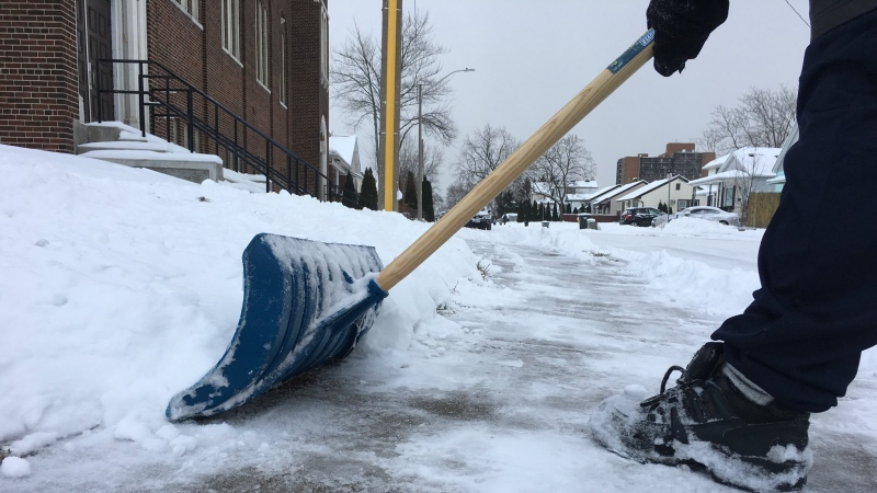 A man shovels snow on Goyeau Street in Windsor, Ont., on Tuesday, Dec. 12, 2017. (Melanie Borrelli / CTV Windsor)