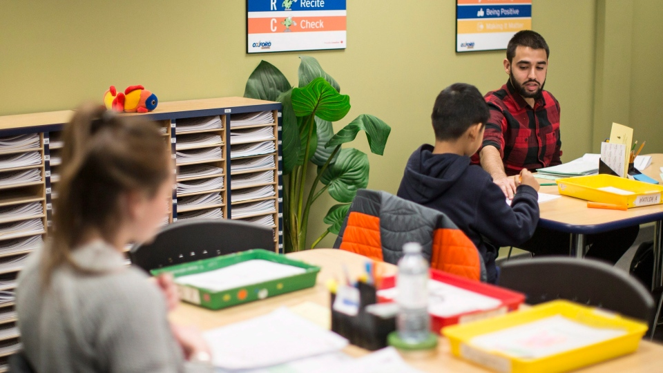 A tutor works with students at an Oxford Learning program in Toronto on Thursday, December 7, 2017. (THE CANADIAN PRESS/Chris Young)
