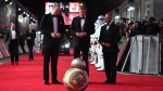 Prince William, left, and Prince Harry, centre, are introduced to a character from the film upon arrival at the premiere of the film 'Star Wars: The Last Jedi' in London, Tuesday, Dec. 12th, 2017. (Photo by Vianney Le Caer/Invision/AP)