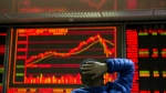 An investor looks at the Chinese market index at a brokerage in Beijing, China, Wednesday, Dec. 13, 2017. (AP Photo/Ng Han Guan)