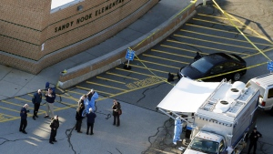 Officials stand outside of Sandy Hook Elementary School in Newtown, Conn. on Dec. 14, 2012. (AP Photo/Julio Cortez)