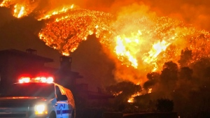 Fire burns canyons and ridges above Bella Vista Drive near Romero Canyon as the fight to contain a wildfire continues in Montecito, Calif. on Tuesday, Dec. 12, 2017. (Mike Eliason/Santa Barbara County Fire Department via AP)