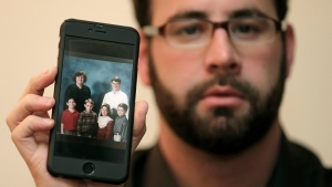 Jamey Anderson holds a photo on his phone of himself, bottom left, at the Word of Faith Christian School with classmates, from left, Liam, Risa Burgeson Pires, and Christopher Davies, and teachers Lisa Brown, top left, and Marty Roper, top right, during an interview in Charlotte, N.C., Monday, Dec. 11, 2017. (AP Photo/Chuck Burton)