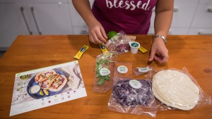 Jayne Zhu lays out ingredients along side an instruction card before preparing a Hello Fresh cajun fish tacos meal kit, at her home in Vancouver, B.C., on Wednesday December 6, 2017. (THE CANADIAN PRESS/Darryl Dyck)