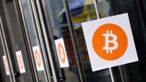 Bitcoin logos are displayed at the Inside Bitcoins conference and trade show, in New York on Monday, April 7, 2014. (AP/Mark Lennihan)