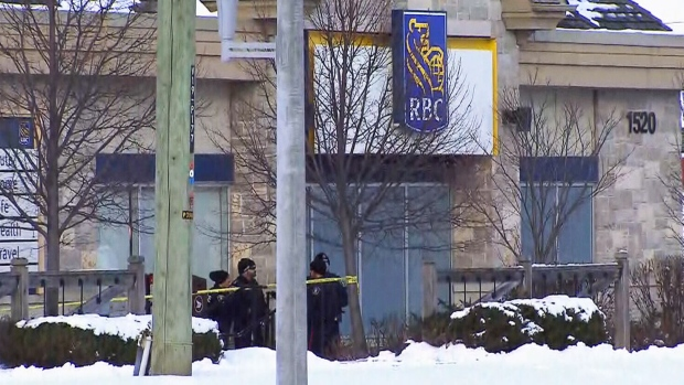 Police officers stand outside a bank in Maple, Ont., where an armed man was killed by police.