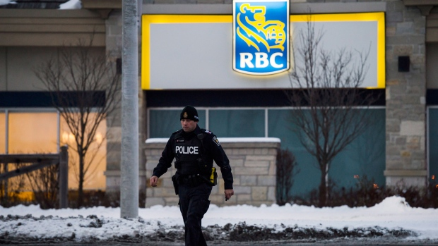 Police secure the area surrounding a bank after a gunman was killed in Maple, Ont., on Wednesday, December 13, 2017. THE CANADIAN PRESS/Christopher Katsarov