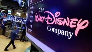 FILE - In this Aug. 8, 2017, file photo, The Walt Disney Co. logo appears on a screen above the floor of the New York Stock Exchange. Disney is buying a large part of the Murdoch family's 21st Century Fox in a $52.4 billion deal, announced Thursday, Dec. 14, including film and television studios, cable and international TV businesses as it tries to meet competition from technology companies in the entertainment business. (AP Photo/Richard Drew, File)