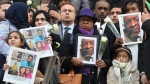 People hold up photos of their loved ones, victims of the fire, as they leave the Grenfell Tower National Memorial Service at St Paul's Cathedral, in London, Thursday Dec. 14, 2017. Britain's royals have joined survivors and families of those who died in London's Grenfell Tower fire for a memorial service to remember the 71 people killed in the June blaze. (Gareth Fuller/Pool Photo via AP)