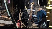 An investigator, standing next to the tail section, looks at the charred remains of a small plane that crashed into a house that was damaged by fire after the plane hit the house in San Diego, Saturday, Dec. 9, 2017. Authorities in southern California say at least two people are dead after the small plane crash. The single-engine, six-seat Beech BE36 Bonanza had taken off from Montgomery Field about a half mile away. (Hayne Palmour IV/The San Diego Union-Tribune via AP)