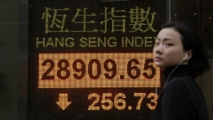 A woman walks past an electronic stock board showing the Hang Seng Index at a bank in Hong Kong, Friday, Dec. 15, 2017. (AP Photo/Kin Cheung)