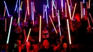 "Star Wars fans raise their lightsabers before the starts of ""Star Wars: The Last Jedi"" movie in Subang Jaya, Malaysia, Friday, Dec. 15, 2017. (AP Photo/Sadiq Asyraf)"
