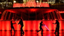 """Star Wars"" fans battle each other with glowing sabers in a fountain at Grand Park during The Glow Battle Tour stop on Friday, Dec. 15, 2017, in Los Angeles. (Photo by Chris Pizzello/Invision/AP)"