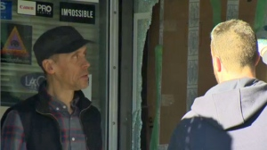 Julian Ferreira, one of the owners of The Camera Store, speaks with a worker replacing a window following a break-in on December 16, 2017