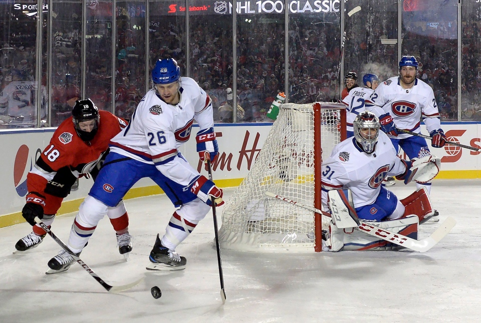 Montreal Canadiens goalie Carey Price (31) keeps an eye on the action as Montreal Canadiens defenceman Jeff Petry (26) tries to clear the puck from Ottawa Senators left wing Ryan Dzingel (18) during second period hockey action at the NHL 100 Classic, in Ottawa on Saturday, December 16, 2017. (Adrian Wyld/THE CANADIAN PRESS)