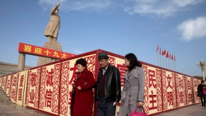 "In this Nov. 4, 2017 photo, residents walk past a statue showing Mao Zedong near billboards with the words for ""Welcome 19th Congress,"" ""Patriotism"" and ""Democracy"" near a square in Kashgar in western China's Xinjiang region. (AP Photo/Ng Han Guan)"