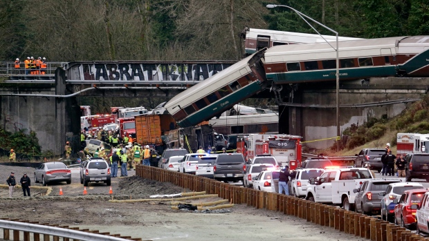 Cars from an Amtrak train lay spilled onto Interstate 5 below as some remain on the tracks above Monday, Dec. 18, 2017, in DuPont, Wash. (AP Photo/Elaine Thompson)
