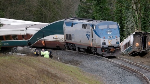 Police officials stand at the back of where an Amtrak train derailed above Interstate 5 Monday, Dec. 18, 2017, in DuPont, Wash. The Amtrak train making the first-ever run along a faster new route hurtled off the overpass Monday near Tacoma and spilled some of its cars onto the highway below, killing some people, authorities said. (AP Photo/Elaine Thompson)