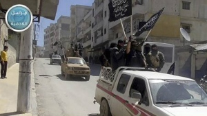 Syria's al Qaeda-linked Nusra Front fighters stand on their vehicles and wave their group's flags as they tour the streets of Jisr al-Shughour, Idlib province, Syria on April 25, 2015. (Al-Nusra Front)