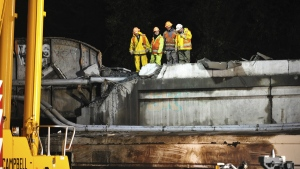 Workers examine a damaged bridge section at the site of the derailment of an Amtrak train in Dupont, Wash., on Dec. 19, 2017.  (Thomas James/Pool via AP)
