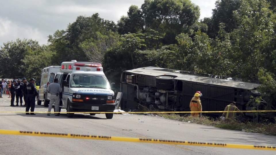 An ambulance parked next to an overturned bus in Mahahual, Quintana Roo state, Mexico, on Dec. 19, 2017. (Novedades de Quintana Roo via AP)