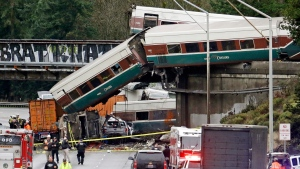 In this Dec. 18, 2017, file photo, cars from an Amtrak train lie spilled onto Interstate 5 below alongside smashed vehicles as some train cars remain on the tracks above in DuPont, Wash. (AP Photo/Elaine Thompson, File)