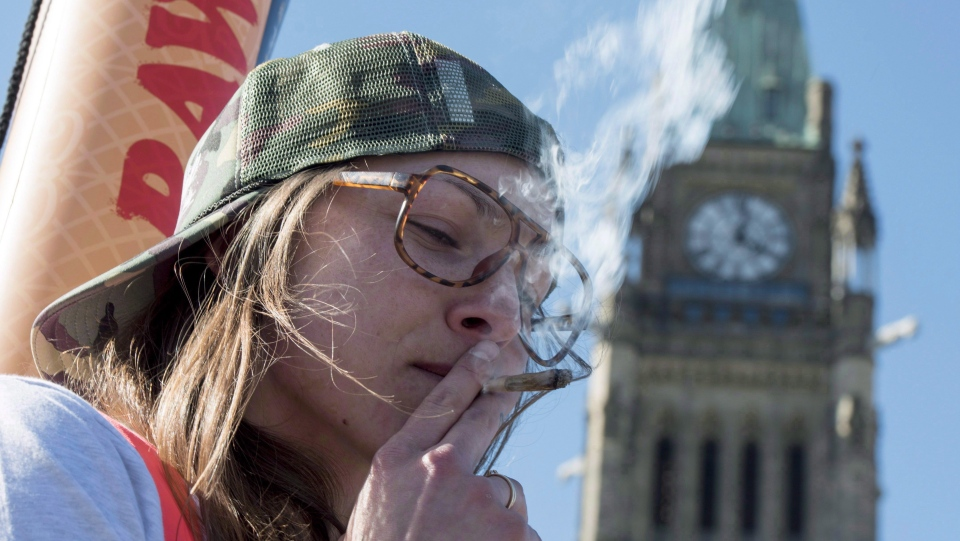 A woman smokes a joint during the annual 420 marijuana rally on Parliament hill on Wednesday, April 20, 2016 in Ottawa. (Justin Tang/THE CANADIAN PRESS)