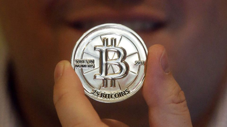 In this April 3, 2013 file photo, Mike Caldwell, a 35-year-old software engineer, holds a 25 Bitcoin token at his shop in Sandy, Utah. (AP Photo/Rick Bowmer)