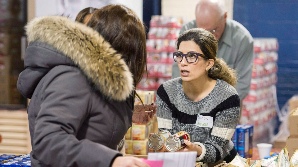 A volunteer, right, offers canned food to a woman at the Welcome Hall Mission in Montreal, Tuesday, March 14, 2017. THE CANADIAN PRESS/Graham Hughes